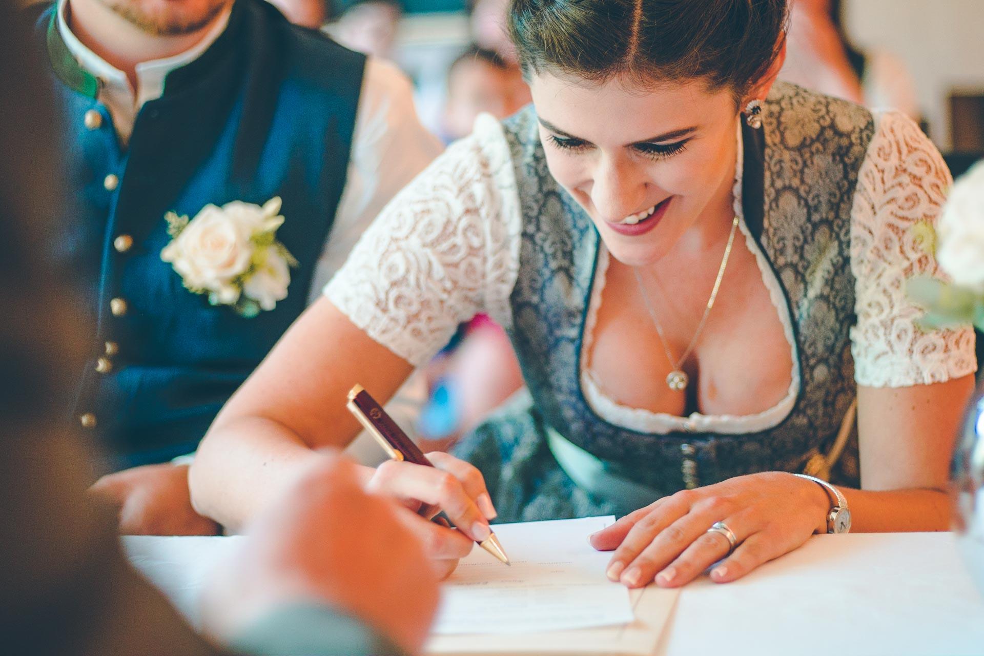 Die Braut unterschreibt im Standesamt