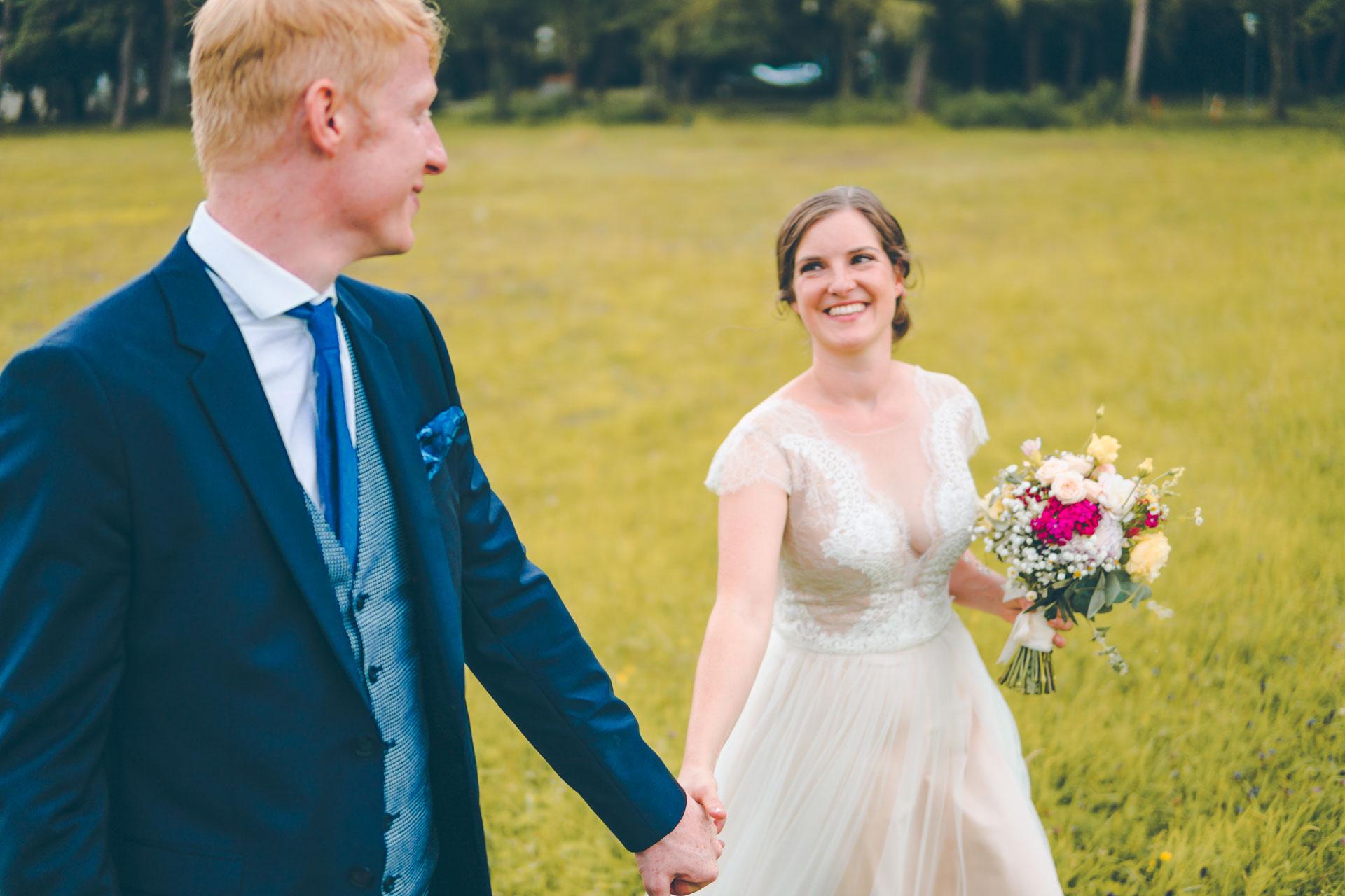 Natürliches Hochzeitsbild des Brautpaars auf einer Wiese