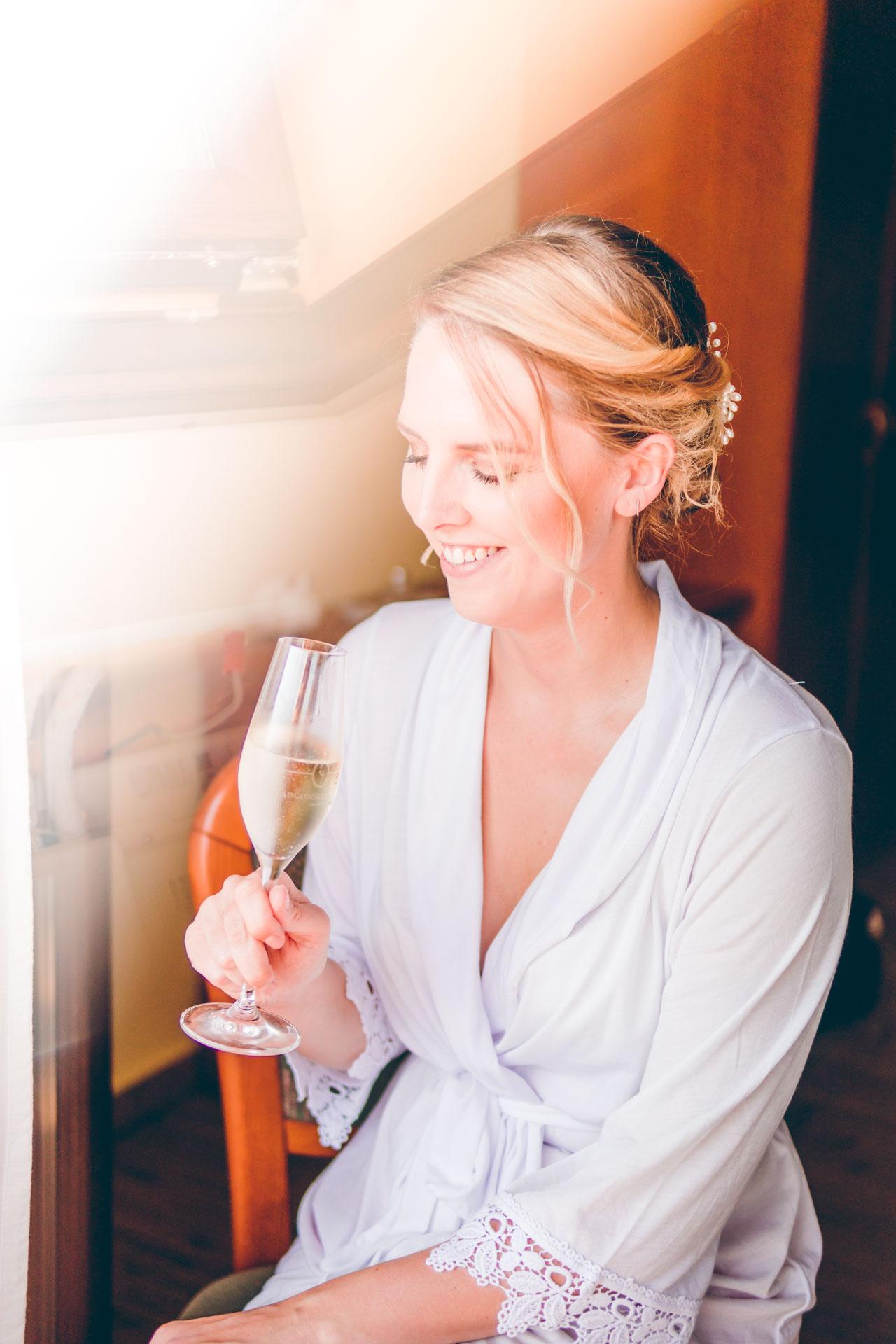 Die Braut trinkt Sekt beim Getting Ready