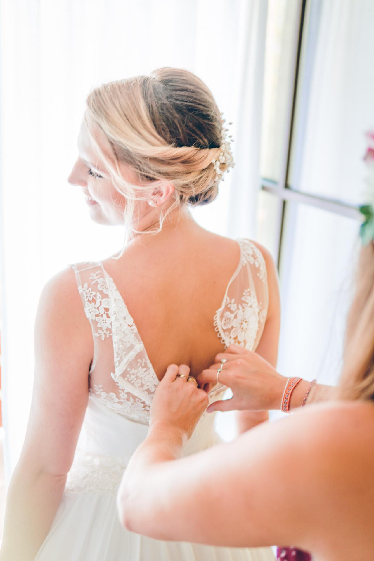 Die Braut und ihre Trauzeugin beim Hochzeitskleid anziehen