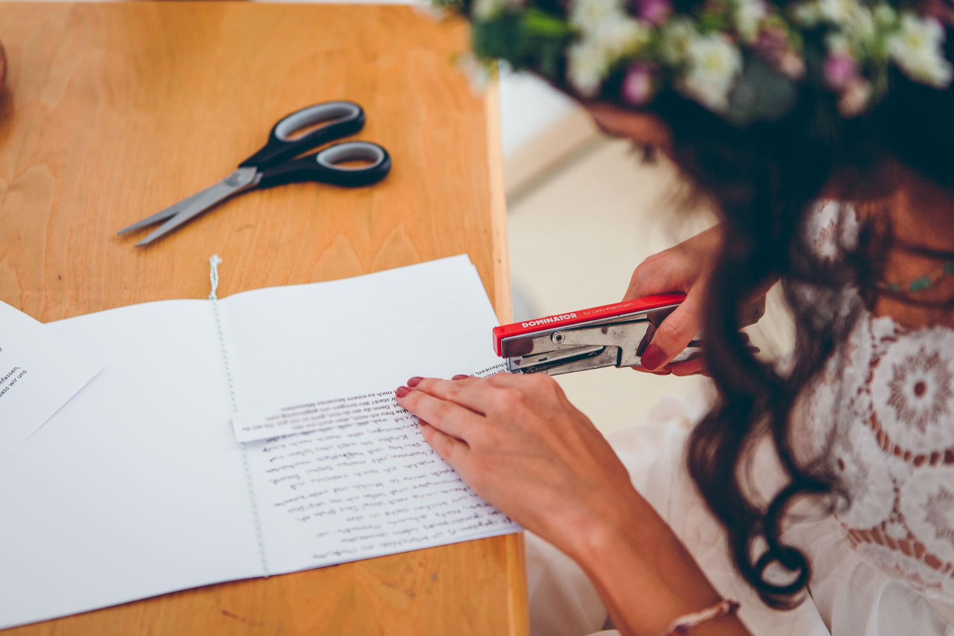 Braut schreibt den Trauschwur im Boho Brautkleid