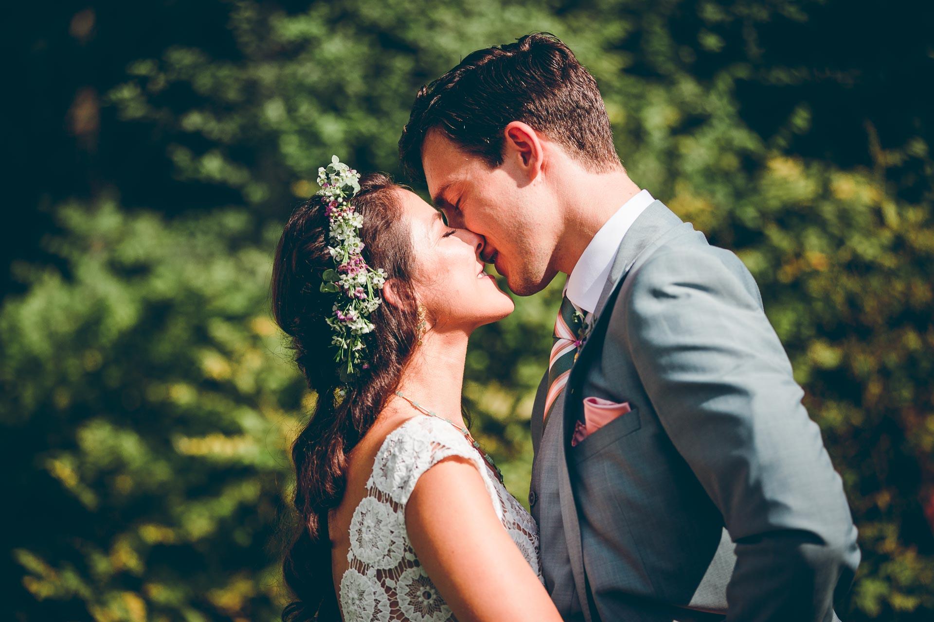 Küssendes Hochzeitspaar auf freier Trauung auf Vintage Boho Hochzeit im bayrischen Blueland