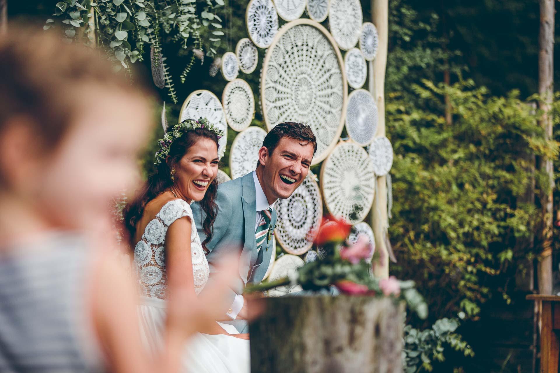Lachendes Hochzeitspaar auf freier Trauung auf Vintage Boho Hochzeit im bayrischen Blueland
