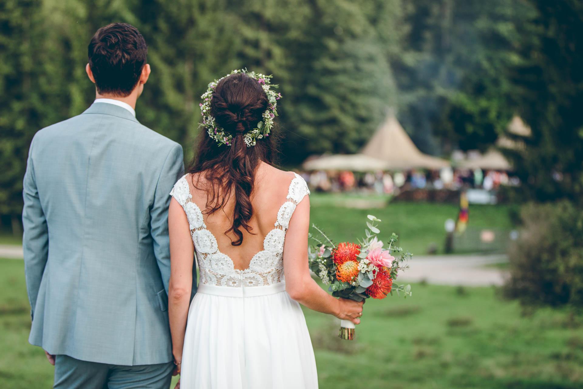 Brautpaar steht vor Blueland Hochzeit mit Zelten