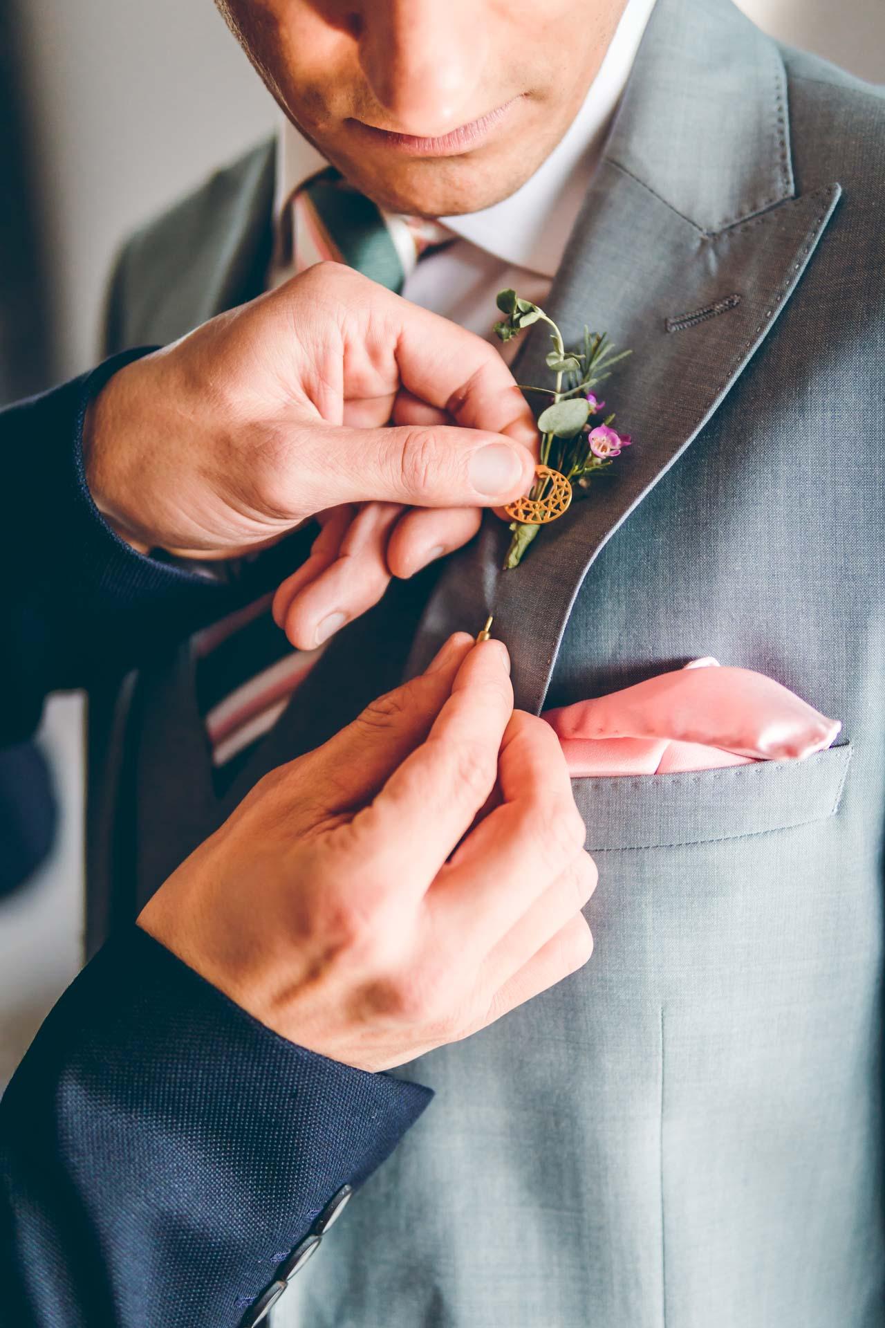 Bräutigam kriegt Deko Stecknadel an den Anzug gesteckt