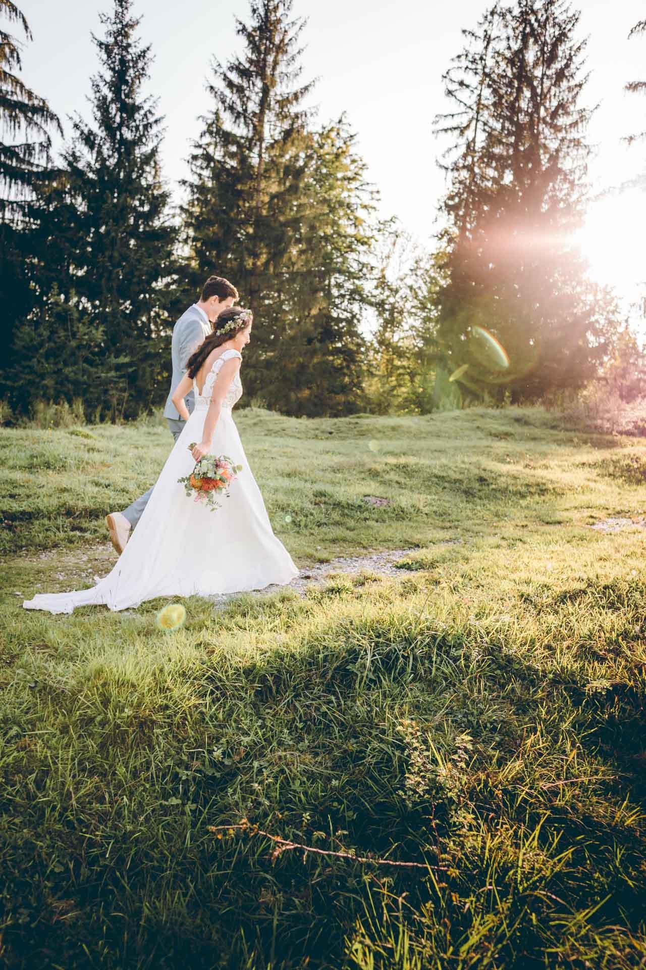 Brautpaar geht über Wiese im Sonneuntergang in Bayern