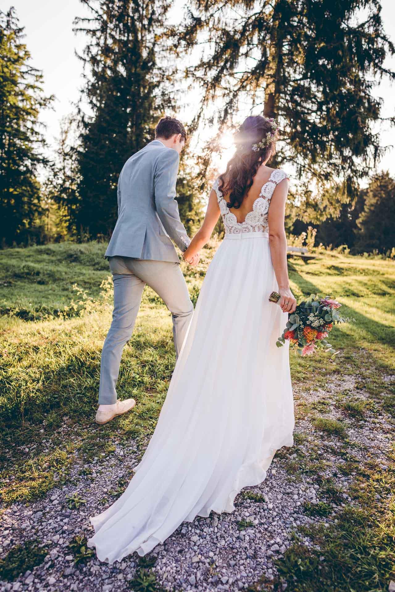 Brautpaar geht über Wiese im Sonneuntergang in Bayern und halten Händchen