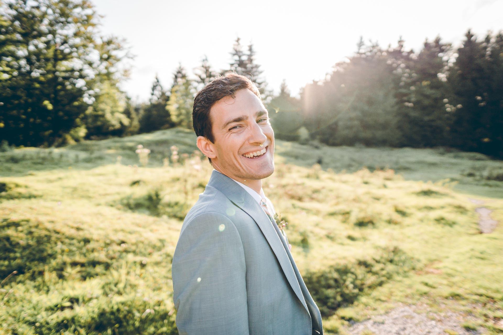 Bräutigam lacht auf Wiese in Bayern in Murnau