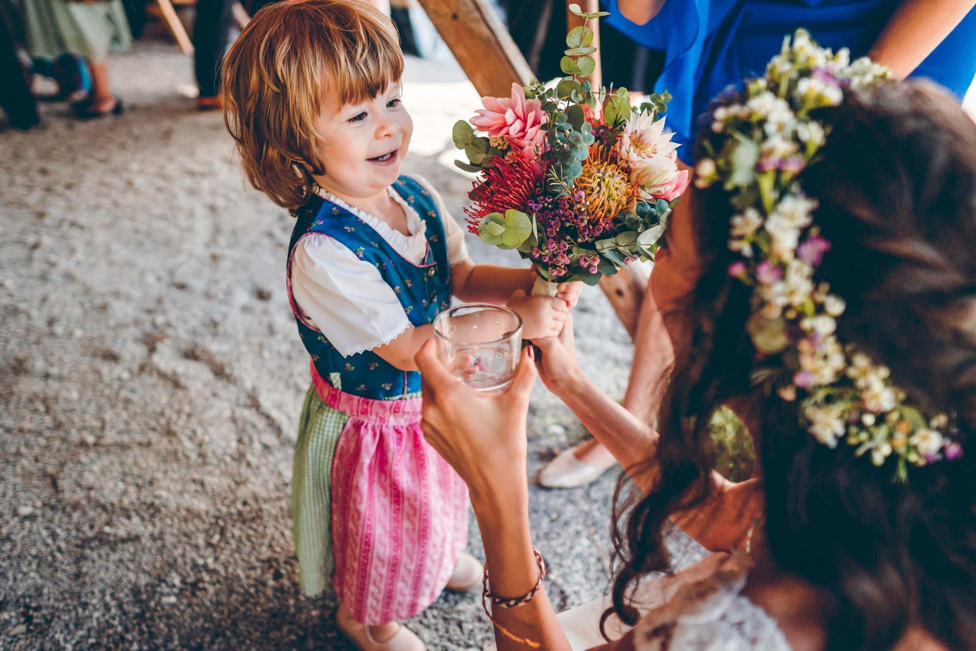 Braut mit kleinem Mädchen und Brautstrauß bei Sommerhochzeit in Bayern