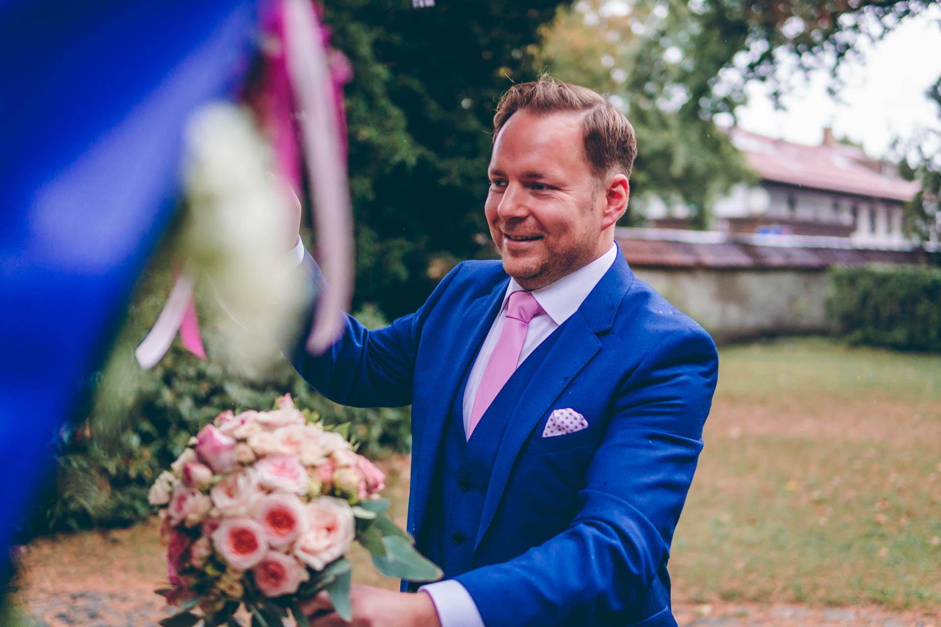 Bräutigam auf Hochzeit in München bei Regen auf Fahrt zur Alten Gärtnerei